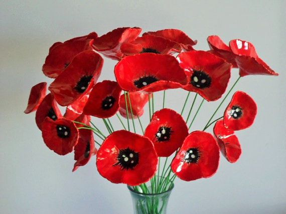 These are gorgeous ceramic red poppy flowers..  The flowers are handmade by myself from clay, fired in a kiln, and hand painted with glaze before their second firing. They are then carefully placed and glued onto a length of green wire. They look lovely as a small bunch in a narrow neck vase..or on masse !   This listing is for 5 flower stems....each wire length is about 25-30cm long and they are all slightly different in size ...largest about 8 cm in diameter. The flower itself is red with…