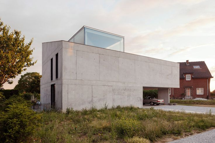 A glass study projects from the roof of this concrete house near Brussels by ISM Architecten, but it presents an austere windowless facade to the street