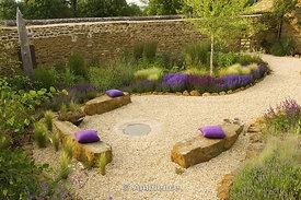 Rickyard Barn giardino, Northamptonshire - vista sul giardino Gravel con sedili di roccia, cuscini, scultura legni, Salvia X Superba, Salvia Wesuwe, Stipa tenuissima, Knautia