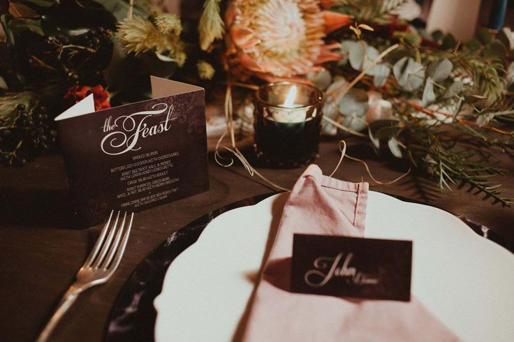 Table setting with our black marble charger plates, white scallop dinnerware, vintage silver cutlery, custom made napkins and finished with menus and place name cards.