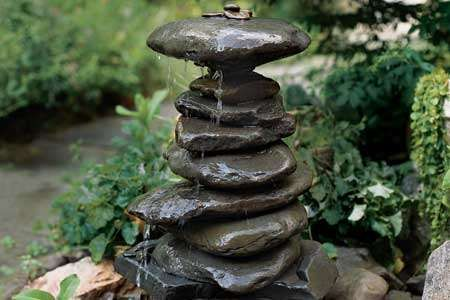 A stacked stone DIY garden fountain. Be interesting to research alternative water
