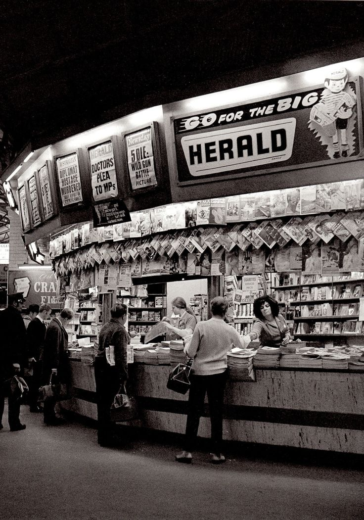 60's MELBOURNE NEWSSTAND Flinders Street Station Melbourne 1969. (PHOTO DETAIL) I love the woman in the big hair selling papers, & cigarettes are openly displayed, you just don't see that anymore. And The Queen on the Women's Weekly cover & the Girlie mags all pinned up. Great photo. From the fabulous book MELBOURNE by Angus O'Callaghan by Ben Albrecht 2015. (visit minkshmink on pinterest)