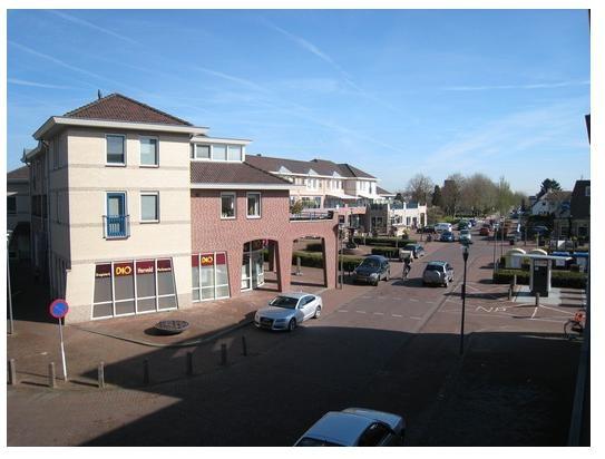 Uitzicht vanuit de woonkamer. Het appartement ligt boven het winkelcentrum in Herveld.