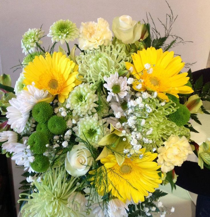 A cluster of budding flowers in a variety of greens and yellow accents.