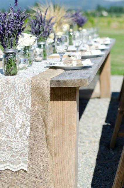 Une table en bois brut, chemin de table en toile de jute et dentelle et pour finir la déco des pots à confiture en guise de vase pour accueillir des brins de lavande. Esprit authentique !