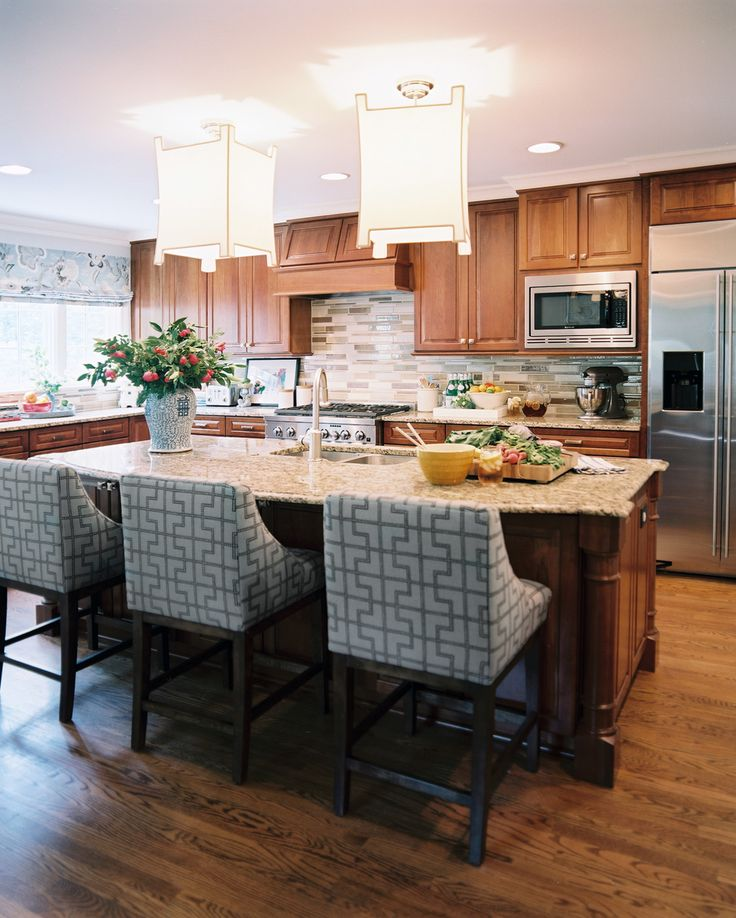 What was once a serious and staid home in Raleigh, NC, received a lively makeover from decorator Jamie Meares (May 2012). While the kitchen is fairly traditional, with granite countertops and subdued wood floors and cabinets, Meares introduced an unexpected pattern in the upholstery of the barstools.
