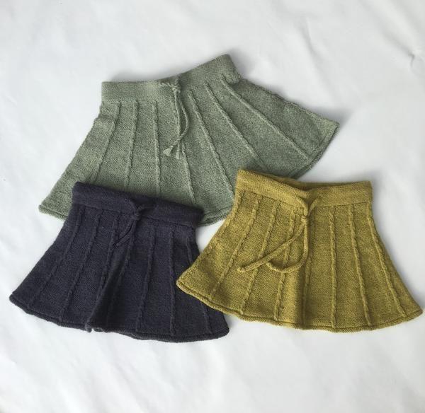 Skøn nederdel i retrostil strikket i det blødeste alpaca garn, som er absolut kradsefri. Nederdelen er strikket i baner, som er adskilt af små babysnoninger, og så har den det helt rigtige 'swing' - præcis som de små piger kan lide det. Nederdelen er meget nemt strikket. Babysnoningerne strikkes uden brug af hjælpepind, så her kan de fleste være med. Nederdelen strikkes rundt på rundpind oppefra og ned, så længden nemt kan justeres undervejs. Der er både elastik og snor i linningen. S...