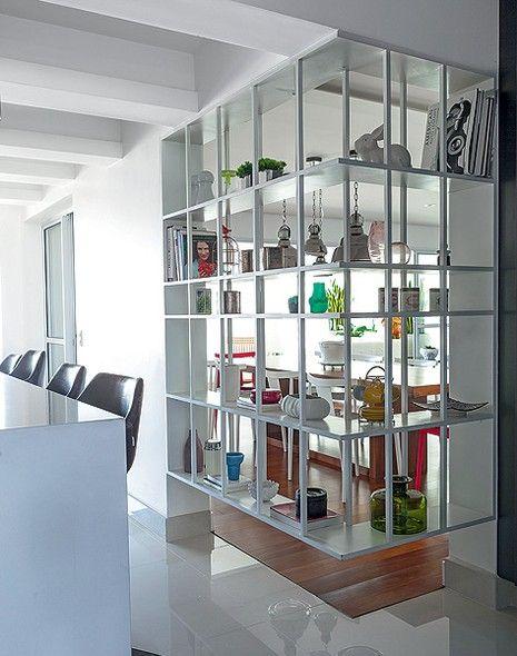 """A estante em L fecha com leveza um canto da sala no projeto da arquiteta Flávia Gerab Tayar. Totalmente vazada para a cozinha, ela é suspensa do chão 38 cm. """"Ela divide os ambientes, mas mantém a integração visual, e é usada dos dois lados"""", diz"""
