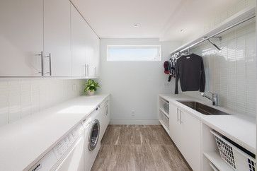Plenty of hanging space and bench space in this modern and sleek laundry design.