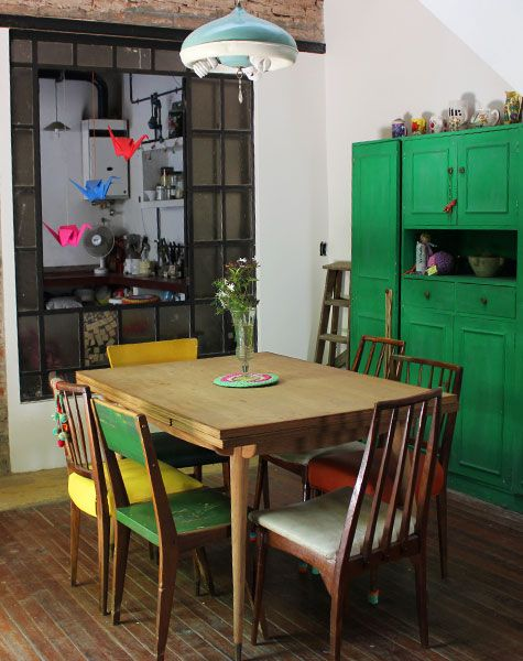 Mesa y sillas recicladas en un ambiente alegre como el día.  Me gusta la división vidriada que separa el comedor de la cocina..