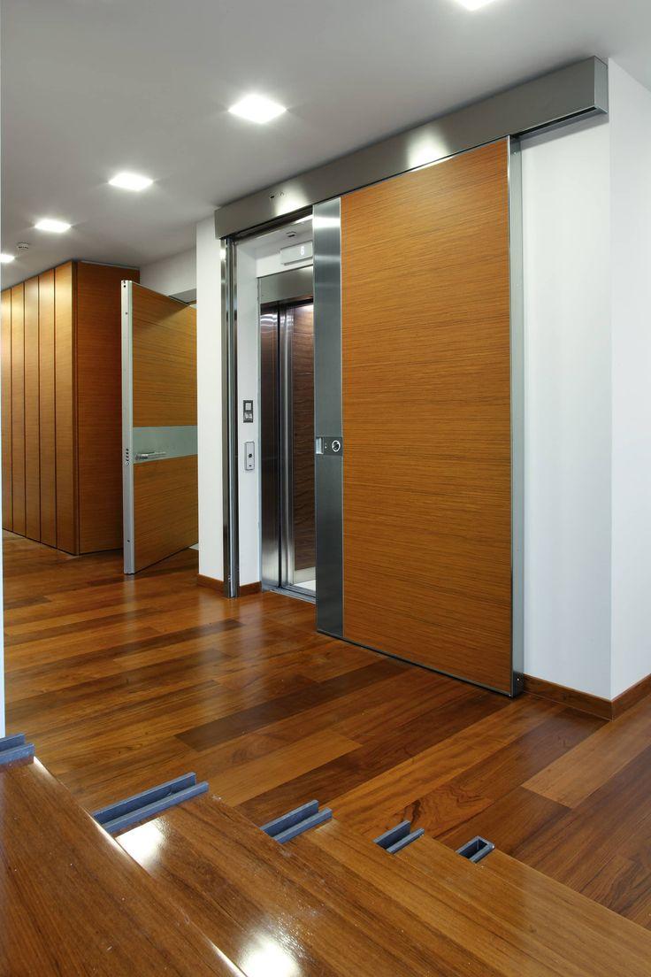 La porta scorrevole blindata Vela a doghe verticali consente di progettare l'anta fino al soffitto e trasformarla in un segno architettonico in movimento.