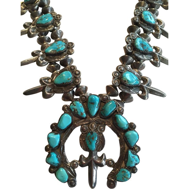 VINTAGE NAVAJO SQUASH BLOSSOM NECKLACE DESCRIPTION: This extraordinary necklace features fleur-de-lis blossoms, which have been hand-stamped and