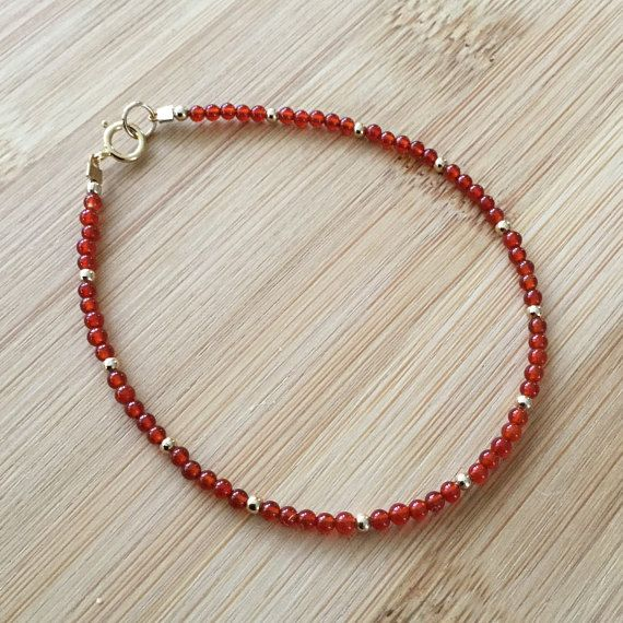 """A narrow bracelet of brilliant red carnelian, interspersed with 14K gold filled beads, is perfect for layering. It also makes a slender, elegant statement when worn alone. The bracelet is 7"""" long and fastens with a gold filled spring clasp. The 2mm beads are quite small, giving"""