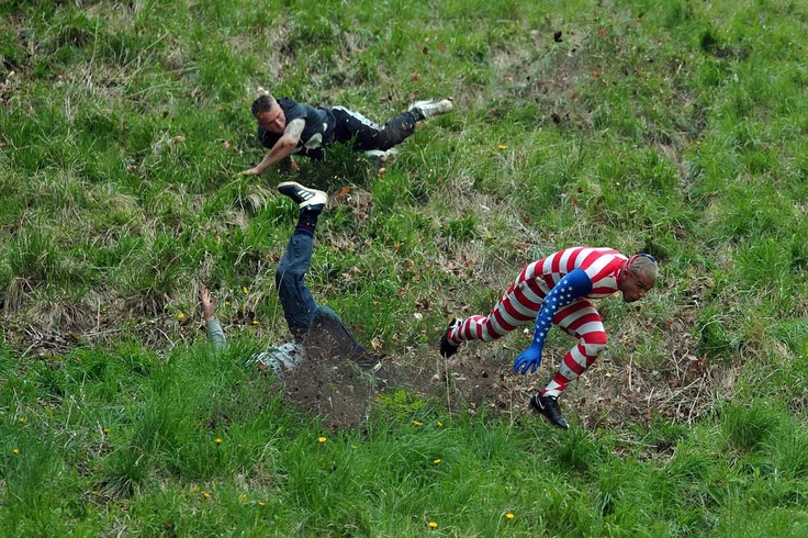 Carl Court—  May 27, 2013. Competitors run and tumble down Coopers Hill in pursuit of a fake foam round Double Gloucester cheese during the annual cheese rolling and wake near the village of Brockworth near Gloucester in western England.