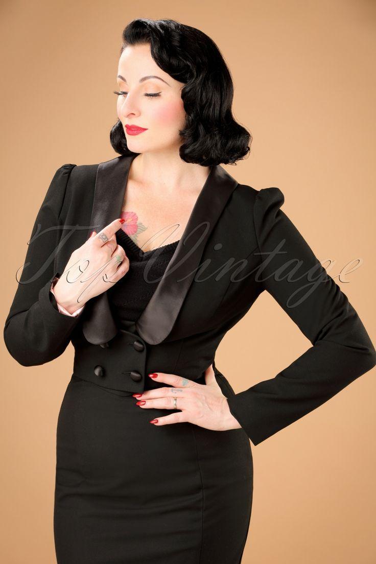Deze 30s Jolie Blazer Jacket in Black is de fabulous vrouwelijke variant van de klassieke herenblazer!  Jolie maakt met haar slanke, cropped stijltje en glanzende satijnen accenten een dikke knipoog naar de jaren 30! De lange licht poffende mouwen, lage afgeronde kraag en double breasted knoopsluiting maken de 'suit-look' helemaal af. Uitgevoerd in een soepele zwarte stof (stretcht niet) en afgewerkt met een lichtroze satijnen voering. Match met een klassieke broek en breng de Marlene...