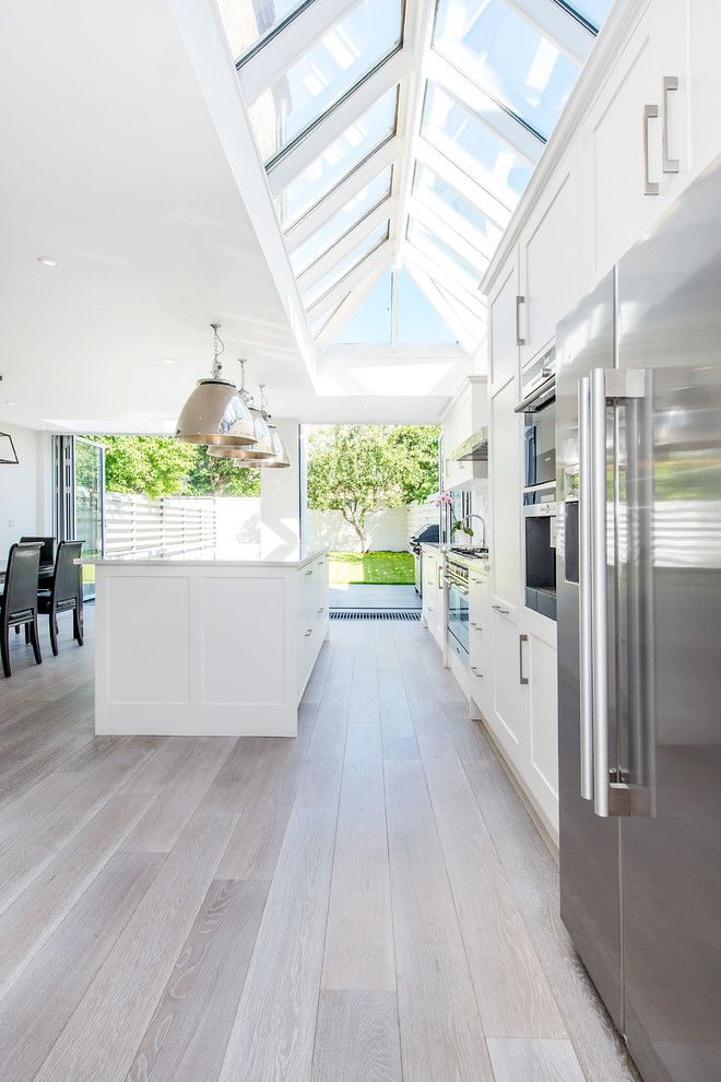 Vaulted sky windows in kitchen, white washed wood floor, white cabinets, large pendants | CATO creative Ltd