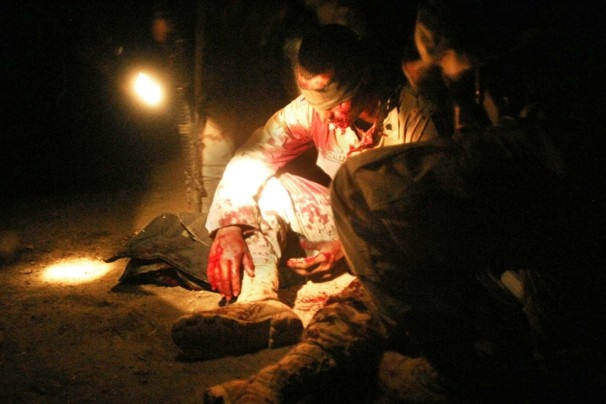 June 22, 2004    A soldier wounded by a shrapnel from a roadside bomb while on a routine patrol in the village of Waidr, about 45 miles east of Baghdad, is treated by media Luis Casas, 22, of Houston.  Andrea Bruce Woodall / The Washington Post