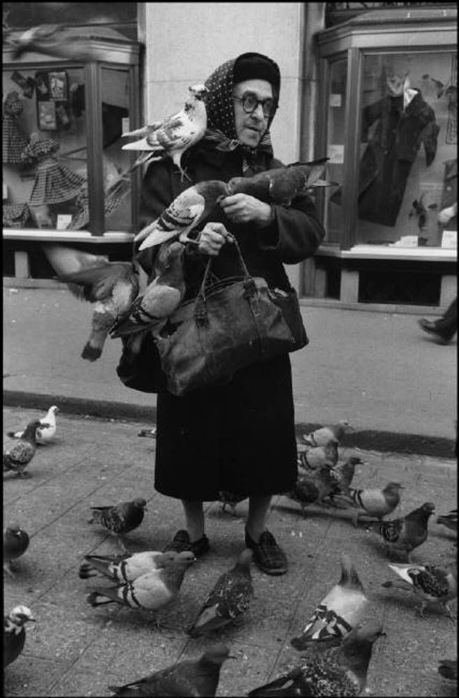 Marilyn Silverstone. Woman feeding pigeons on the Champs Elysees, Paris, 1956