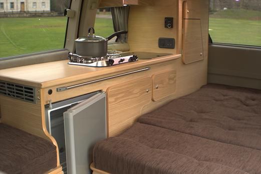 Nissan Elgrand Executive Deluxe interior with bed down and fridge ajar