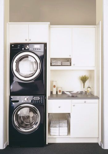 stackable washer and dryer with cabinets on other side. mini fridge and