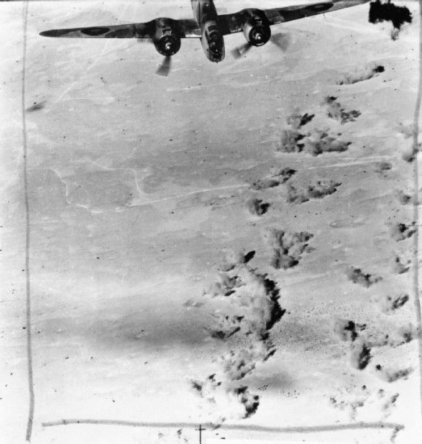 A Martin Baltimore of No. 55 Squadron RAF flies over the target area as salvoes of bombs explode on tanks and motor transport of the 15th Pa...