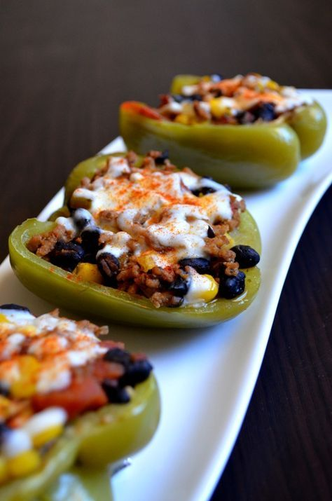 Sante Fe Stuffed Peppers  FOR THE FILLING 1/2 lb. lean ground turkey 1 tbsp. garlic, minced 3 tbsp. chopped onion 2 tbsp. cilantro 3 tbsp. taco seasoning 1/8 c. chopped jalapeno peppers Salt to taste 1 (15.25 oz) can of black beans, rinsed and drained 1 (14 oz) can of tomatoes, drained and rinsed 3/4 c. frozen corn  FOR THE PEPPERS 3 bell peppers, cut in half lengthwise and cleaned* 1/3 c. chicken broth Shredded cheese for garnish* Paprika for garnish (optional)