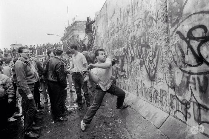 Deze foto is gemaakt op de dag van de val van de Berlijnse muur. Je ziet hier een man die de muur kapot wilt maken. De muur heeft familie's en vrienden uitelkaar getrokken. Veel mensen hadden dan ook heel veel woede voor de muur en voor de regering die de muur daar heeft geplaatst. Je ziet aan de man zijn gezichts uitdrukking dat hij erg boos is en dat hij de muur zo snel mogelijk weg wilt hebben omdat hij zijn vrijheid terug wilt.