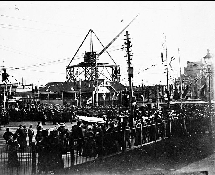 Construction of Flinders Street Railway Station. There is a large crane on a platform in the background, and in the foreground large crowds lining Swanston Street. Bunting on poles make the occasion seem quite 'festive'!