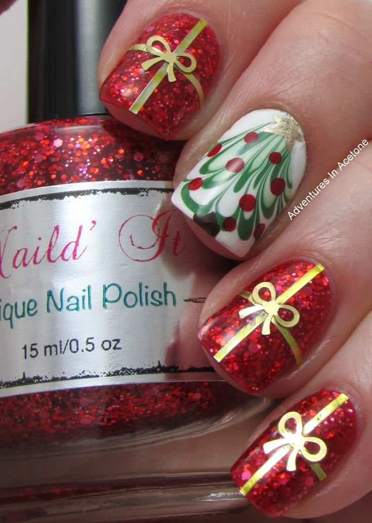 Red sparkle nails tied up with a bow like a present with a Christmas tree to accent.