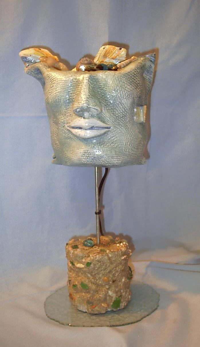 """SCULTURA LUMINOSA """"VIAGGIO NEL SE' """" Scultura luminosa realizzata in  ceramica, metallo, vetro sabbiato, pasta di vetro, vetri levigati dal mare, malta, sabbia e conchiglie.  Dimensioni: larghezza cm.25 altezza cm. 55"""