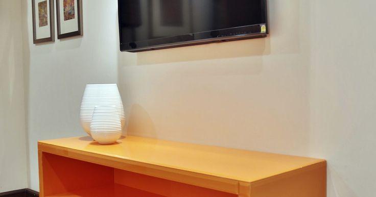 Cómo colgar un televisor de pantalla plana escondiendo los cables. Montar un televisor de pantalla plana en la pared ahorra espacio en el piso de un cuarto, pero ver los cables colgando del muro al aparato puede hacer que la habitación se vea desorganizada y revuelta. Siguiendo estos pasos para pasar el cable a través de un panel, puedes darle a tu cuarto esa apariencia limpia y ordenada, sin que se vea nada más ...