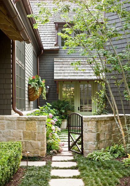 Traditional Exterior by Land Plus Associates, Ltd Add a gate. A low masonry or wood fence paired with a wood or metal gate can add presence to your home's exterior. When accompanied by landscaping in front of and beyond the gate, it draws the eye in, making even a small front yard feel deeper.