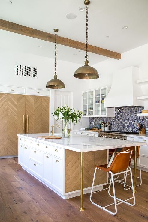 Dana Benson Construction - Gorgeous contemporary kitchen features two brass industrial pendants hung from a white ceiling finished with rustic wood beams over a white island accented with wood herringbone panels and brass legs fixed under a white marble countertop holding a overmount prep sink with a brass hook and spout faucet.