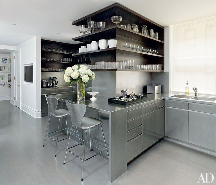 Architect and decorator David Mann equipped a kitchen with custom-made stainless-steel cabinetry and counters that he offset with walnut shelves. | Architectural Digest