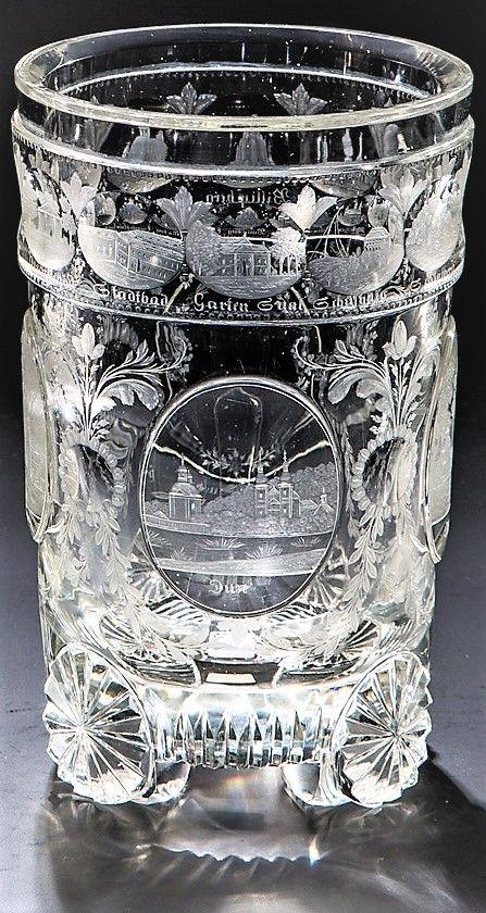 Farbloses, schliffverziertes, auf vier Knollenfüßen ruhendes Glas. Auf der Wandung vier Hochschliffmedaillons, darüber Kugelreihe mit insgesamt 15 geschnittenen, teils polierten Ansichten von Teplitz, jede einzelne bezeichnet. H. 15,5 cm  Böhmen, um 1835 oder später