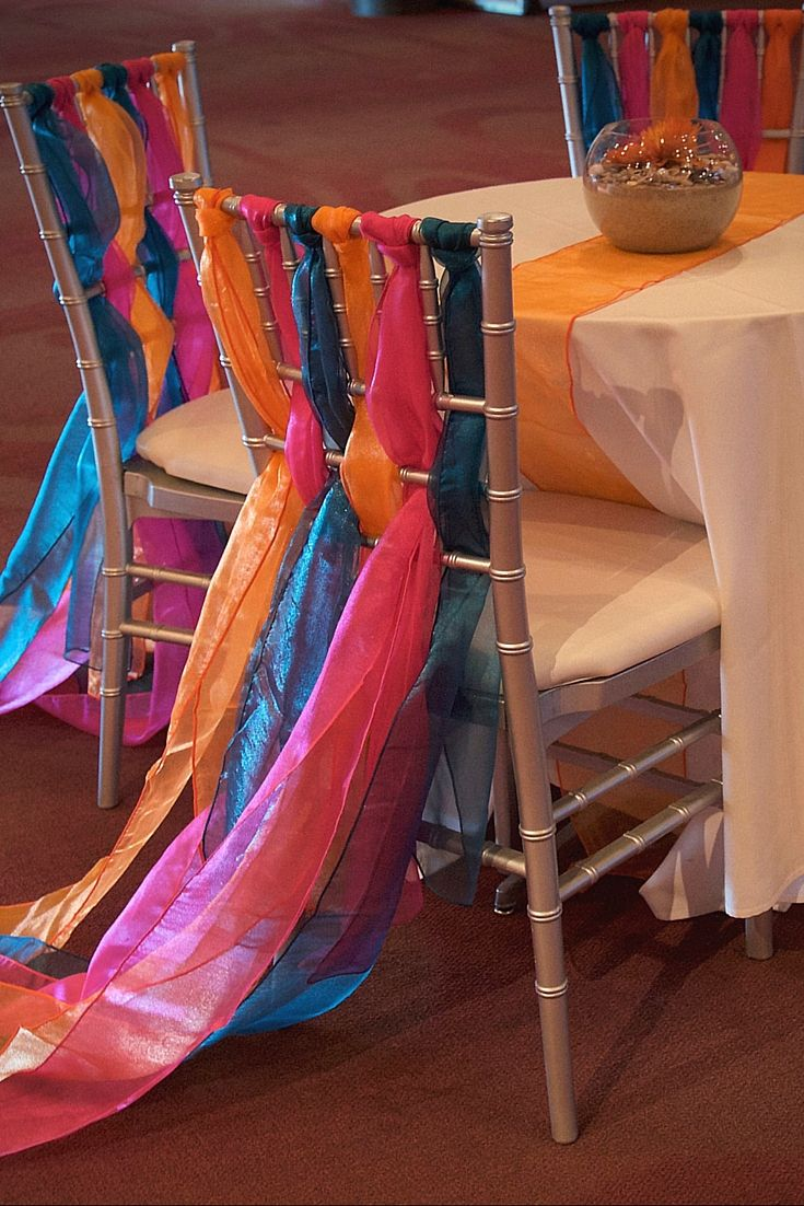 Vibrant Sashes on elegant silver Chiavari chairs create the essence of movement for this Under the Sea inspiration.