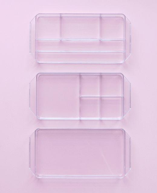 Obrázok GIF priehľadnej škatule s perami, papierom a inými zabalenými kancelárskymi potrebami.