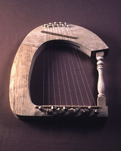 Greek harp,400 AC The frame harp of the fourth and fifth centuries had an arched sound box and a post for support on the open ends and was played resting on the left knee while the player was seated. It was designed having between nine and eleven strings and so that the left hand stroked the farther, longer strings while the right plucked the closer, shorter ones. Decoration varied widely: a harp might be covered with ornate drawings of animals or it might be plain and almost bare.