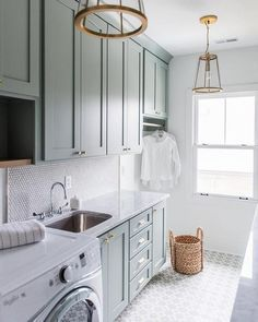 Gray green laundry room cabinets accented with brass knobs are fixed above a curved stainless steel sink paired with a polished nickel gooseneck faucet mounted in front of a white penny tile backsplash to a carrera marble countertop complementing gray green lower cabinets.