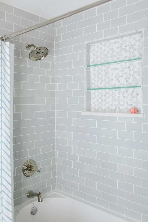 Lovely bathroom features a drop-in tub with shower accented with gray  subway tile surround fitted with a marble hex tiled niche lined with glass  shelves ...