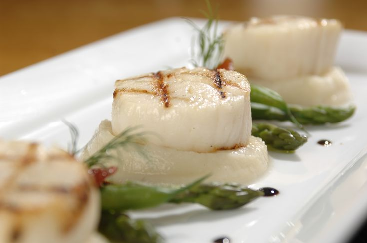 Grilled sea scallops with cauliflower purée, candied tomatoes, asparagus and basil pesto vinaigrette