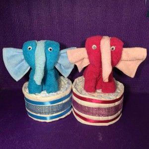 Luiertaart met olifant. Een balancerende olifant op een luiertaart met o.a. een slab, spuugdoekje en een handdoek. Kijk voor meer leuke kraamkado's op.....