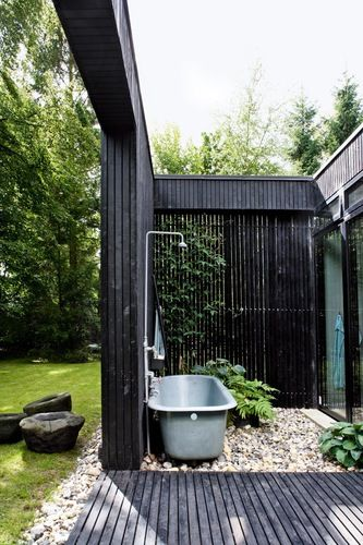 modern cabin, outdoor bathtub and shower, black house