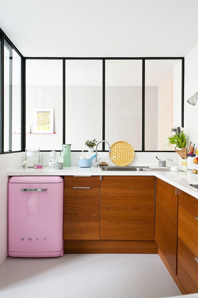 Bright and white kitchen with wood cabinets and small pink mini fridge
