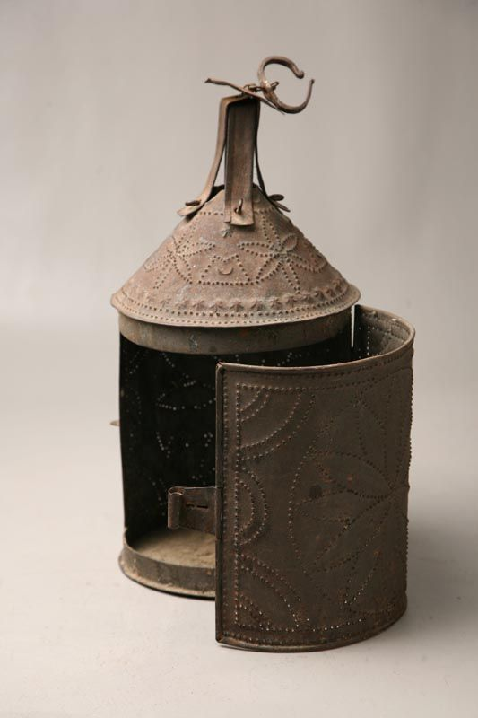 "PUNCHED TIN LANTERN.  19th Century. Large candle lantern with good punched design of compass stars. Scrolled wrought iron hanger. 15 1/2""h."