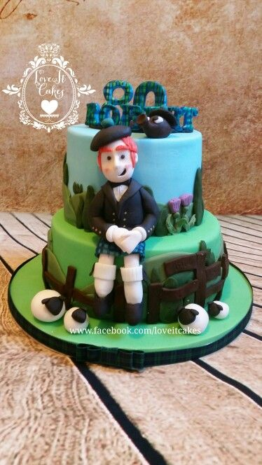 Scottish highland themed 2 tier cake, with scottish man in blackwatch kilt, thistle and fun character haggis, sheep on base to complete the look.