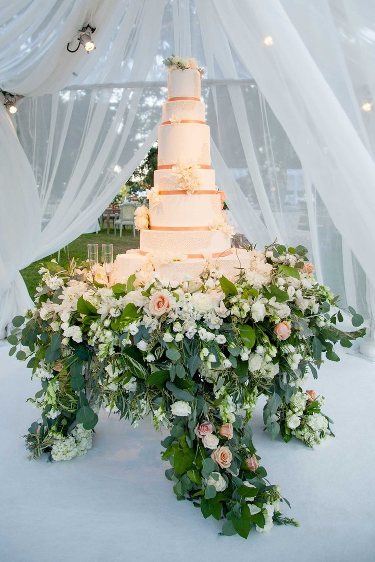 Tall white wedding cake with rose gold ribbon fresh flowers flower cake stand display