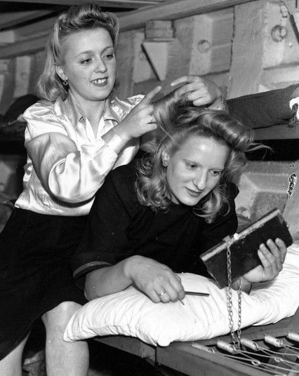The London Underground in Wartime 1944: Miss V Dryden having her hair done by Miss K Lambourn in a London Underground bomb shelter