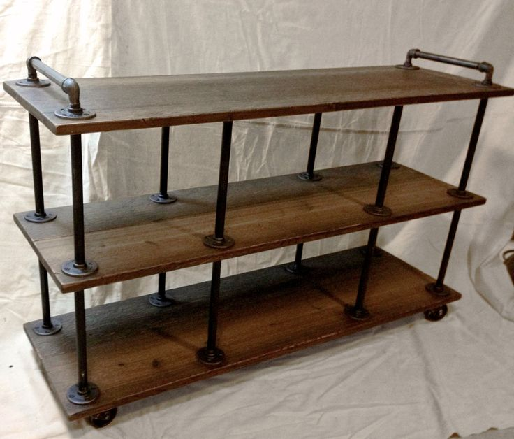 This beautifully finished Industrial TV Stand is made from rough-cut cedar, iron pipe, and iron fittings. The sturdy shelves sit on 3 iron castor wheels for functionality and added industrial style. Dimensions of the TV Stand are 32 high x 52 long x 16 wide and it is made for 46 to 52 TVs. This item is made to order. This item is made to order. Each TV stand will vary slightly in wood grain and stain from the pictures. Custom orders accepted!  For smaller TVs…