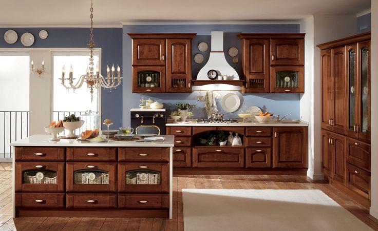 Cucina in legno scuro con la cappa d'arredo e isola centrale che ricrea un'atmosfera calda e avvolgente come un abbraccio.